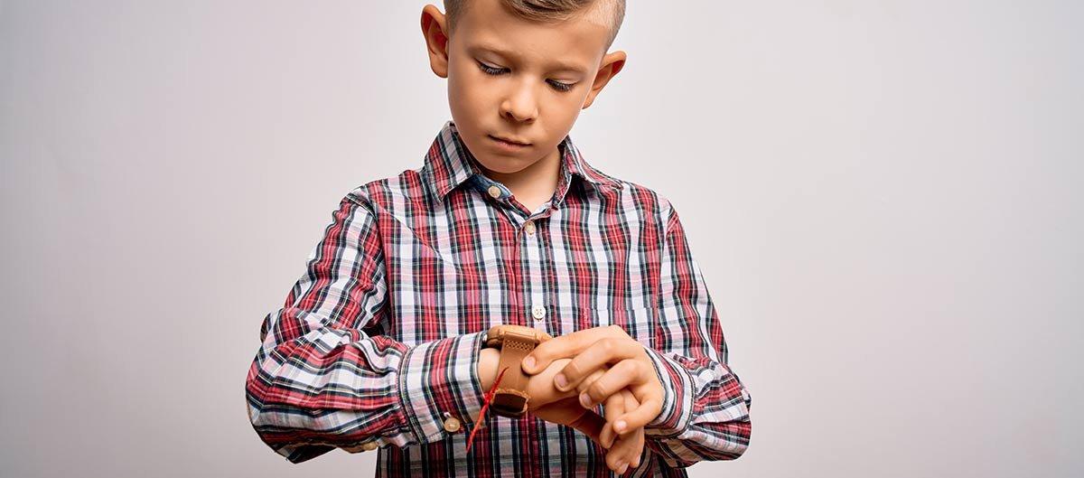 Kind schaut auf analoge Uhr